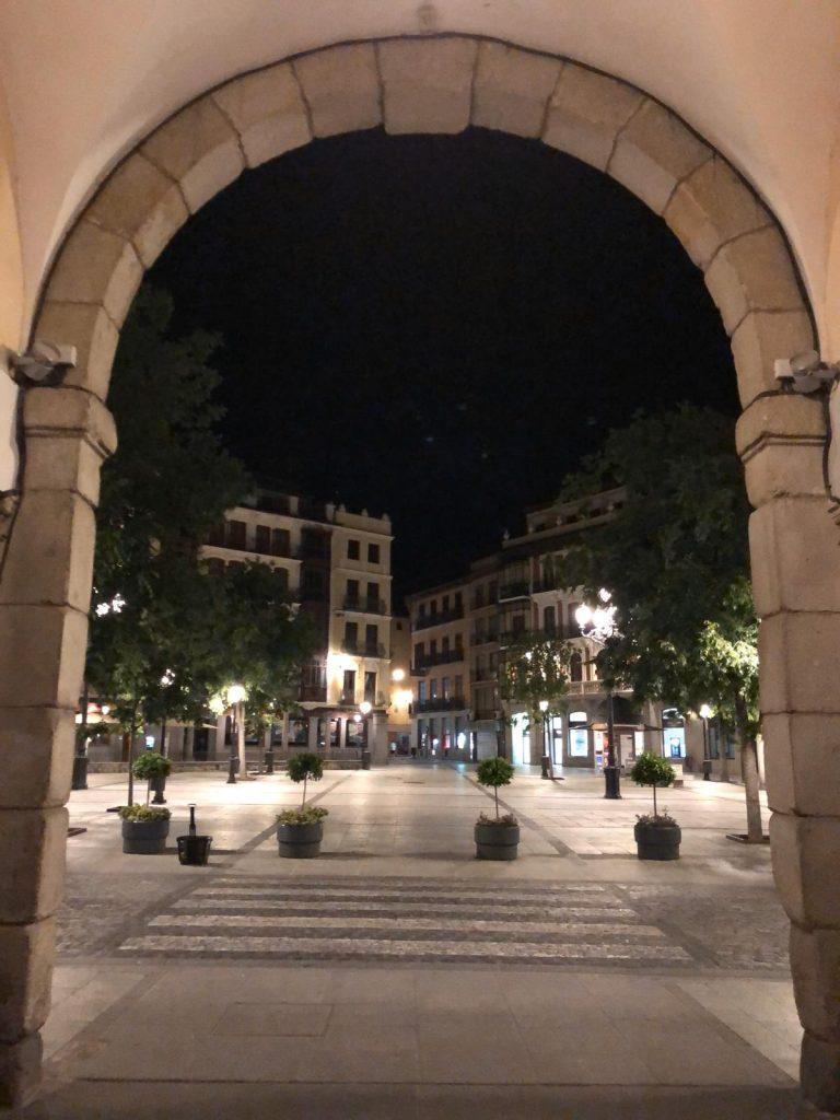 Bajo el Arco de la Sangre, observando una plaza de Zocodover vacía.