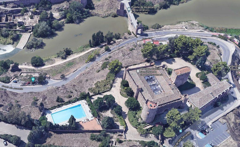 Vista aérea del Castillo de San Servando en Toledo, donde se observa su piscina y el Puente de Alcántara (arriba) Fuente: GoogleMaps