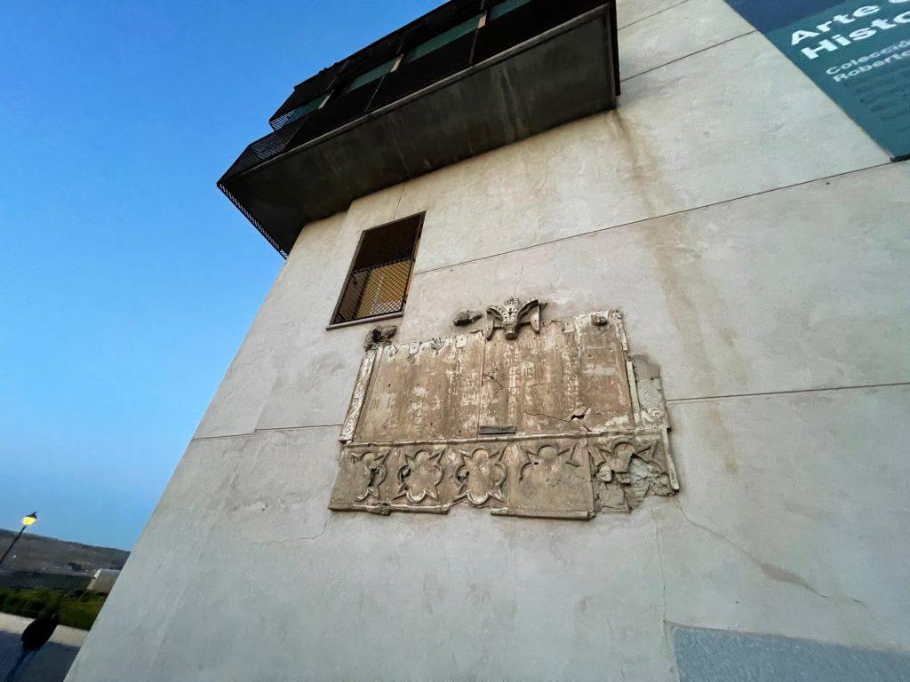 """Tablero de escayola que recuerda el nacimiento de Alfonso X en los Alcázares reales ubicados en esta zona del Miradero, en 1221 (puesta aquí en 1921 por la Real Academia de Bellas Artes) A duras penas se lee: """"En estos que fueron Alcázares reales /nació en 23 de noviembre de 1221/ Don Alfonso el Sabio/ En igual día de 1921 le erige esta lápida/ la Real Academia de Bellas Artes."""""""