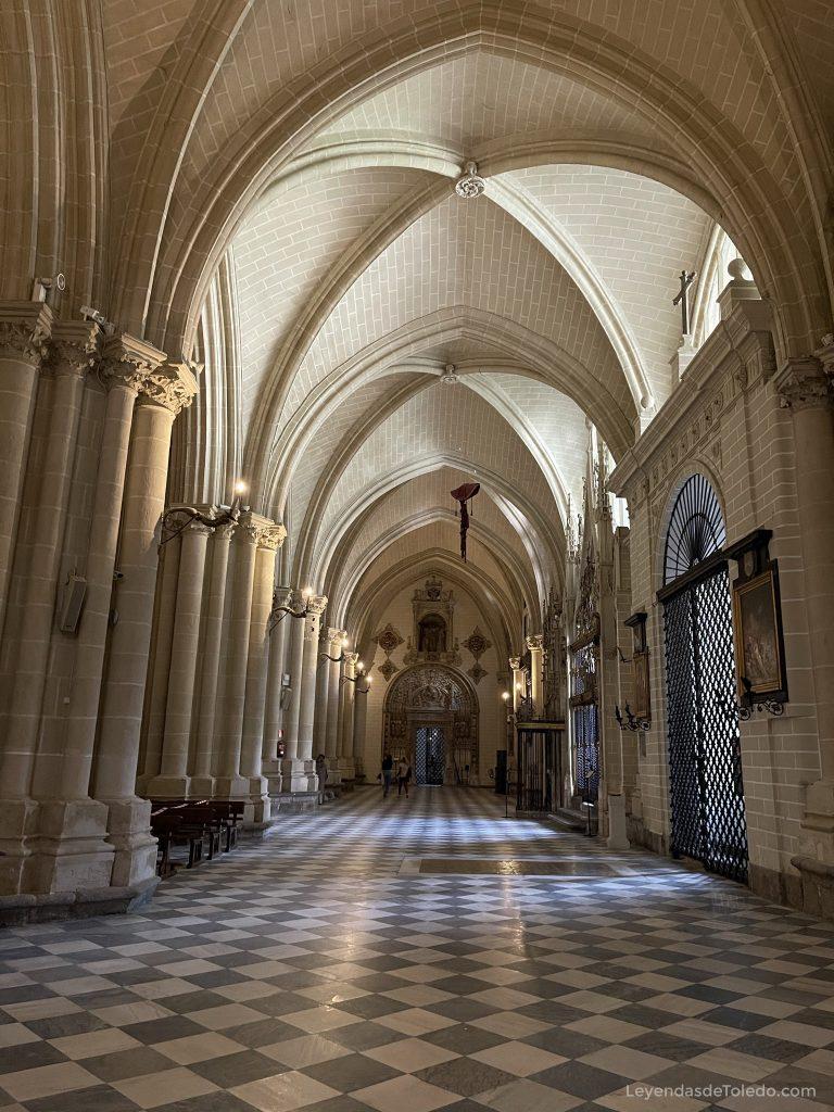 Una de las naves laterales de la Catedral de Toledo, donde observamos un sepulcro y un capelo que aún no ha caído.